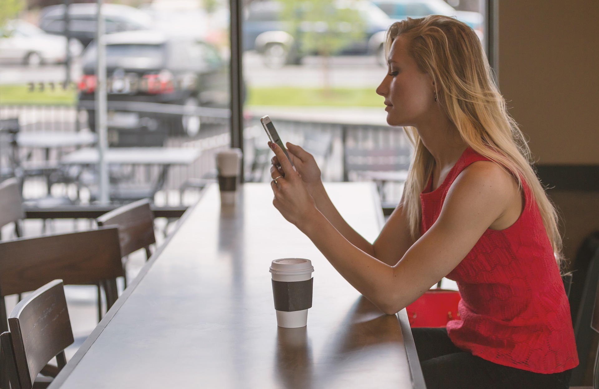 Woman in café looking at her mobile phone