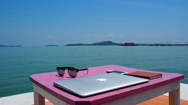 Sunglasses, laptop, phone, and notepad on a pink desk overlooking the sea